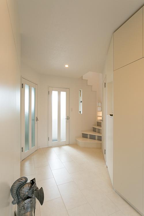 玄関を入ると真っ白なホール。奥のドアは地階に通じる[施工エリア:新潟県糸魚川市]