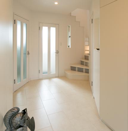 玄関を入ると真っ白なホール。奥のドアは地階に通じる