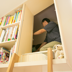 本棚の一部は、並んだ本を出せば屋根裏収納庫の 入り口に