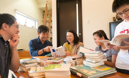 右から朝日学さん、カネタ建設猪又社長、仁美さん、娘の千智さん、息子の遼太くん。 ご家族お勧めの本を囲んで。